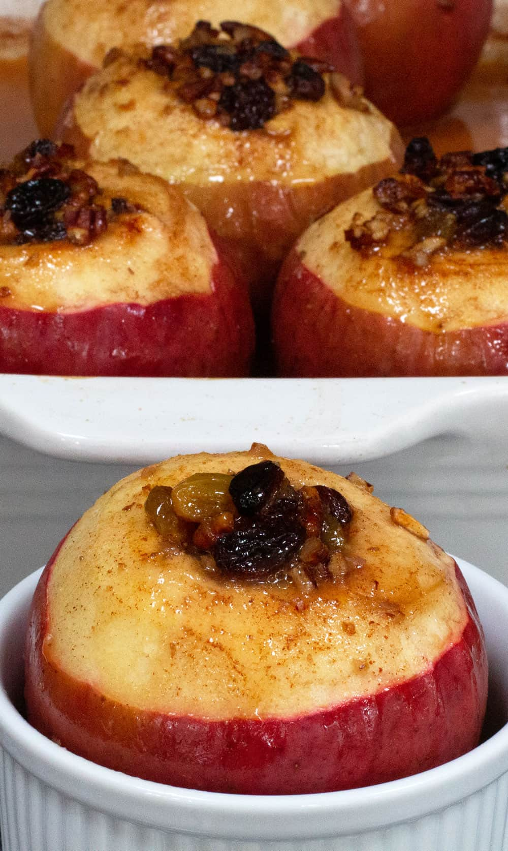 Simple oven-baked apple in a ramekin front of a baking dish with other baked apples