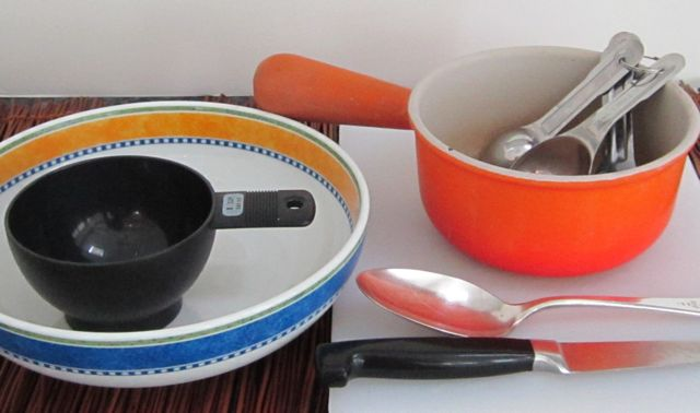 equipment to make fruit topping, bowl, cutting board, knife, measuring spoons, measuring cup, small pot