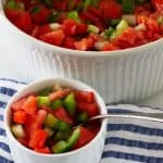 a ramekin of Greek salad with a serving bowl of salad behind