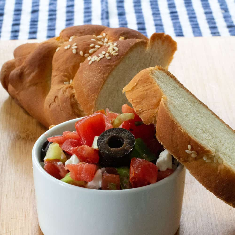 a small ramekin of Greek salad with challah, including a slice leaning on the salad