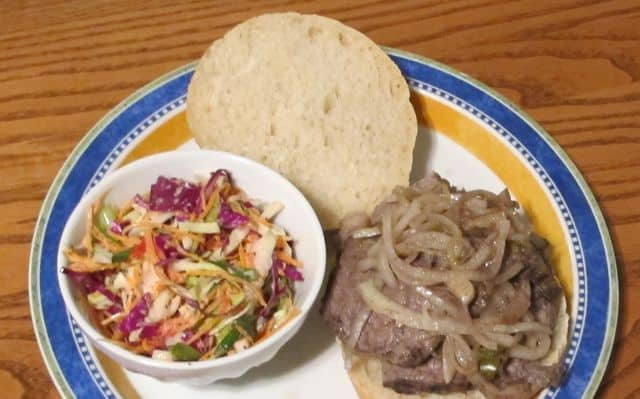 slow cooker pot roast sandwich with cole slaw on a plate