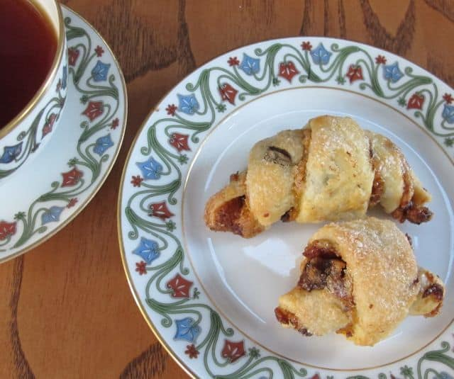 rugelach on a plate with cup of tea