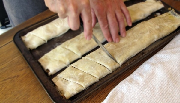 cutting rolled baklava into pieces