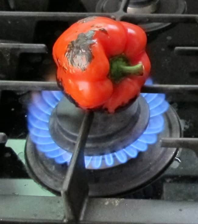 roasting a red pepper over an open flame on cooktop