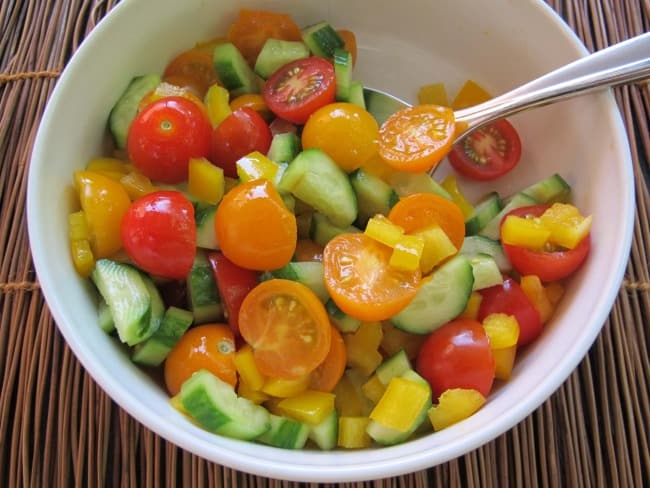 mixing vegetables for cherry tomato and cucumber salad