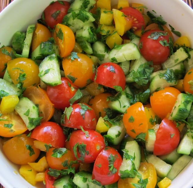 adding chopped parsley to cherry tomato and cucumber salad