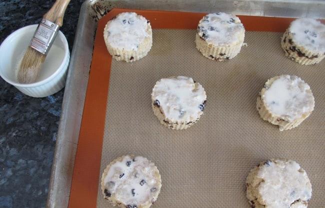 Brushing currant scones with cream