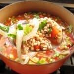 adding ingredients to mushroom barley soup