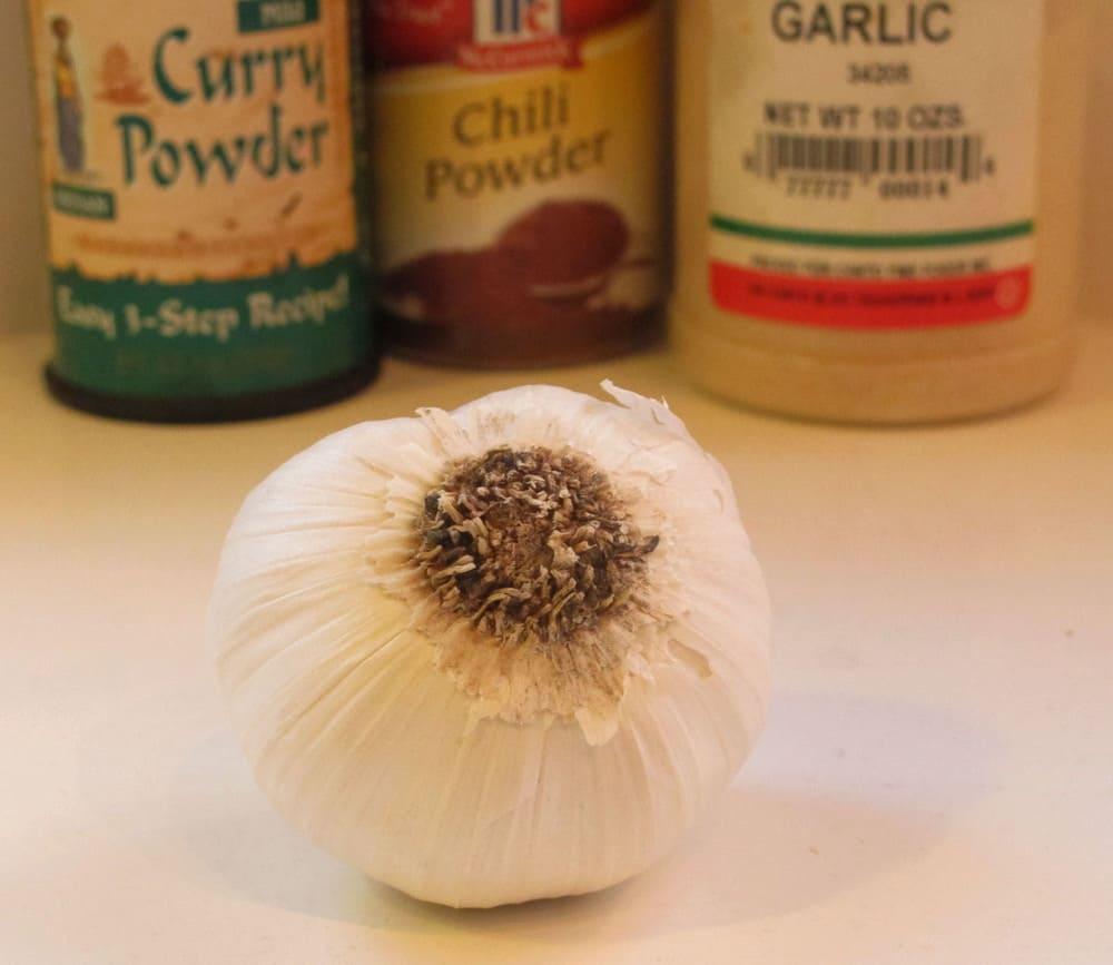 head of garlic in front of curry powder, chili powder and garlic powder