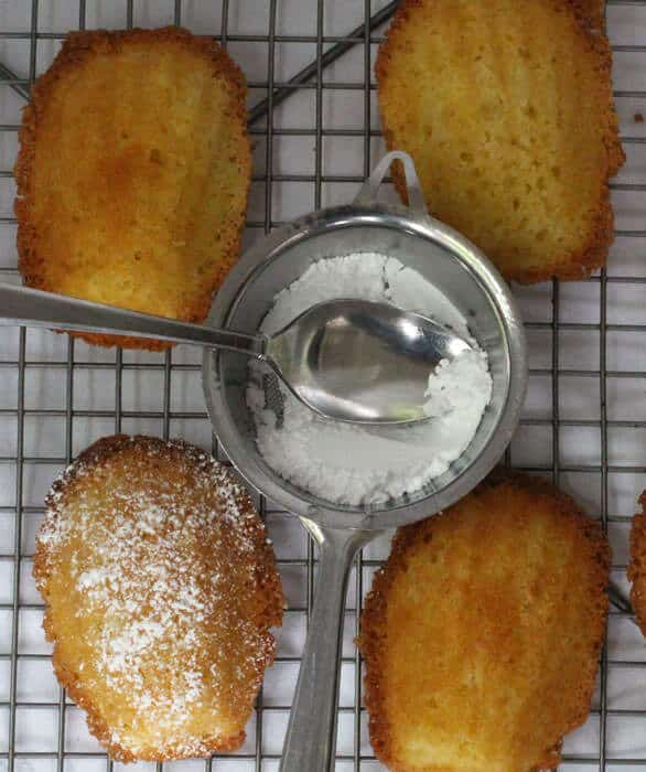 ginger-infused madeleines being sprinkled with confectioner's sugar