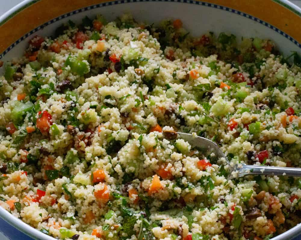 adding dressing to minty couscous salad