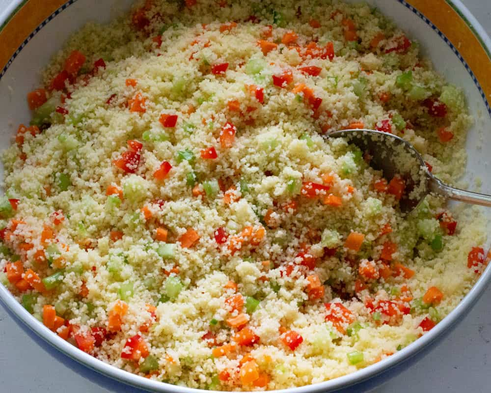 adding vegetables to cooked couscous
