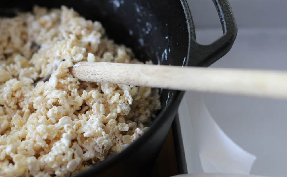 Scooping the rice krispy mixture into the parchment-lined pan | Mother Would Know
