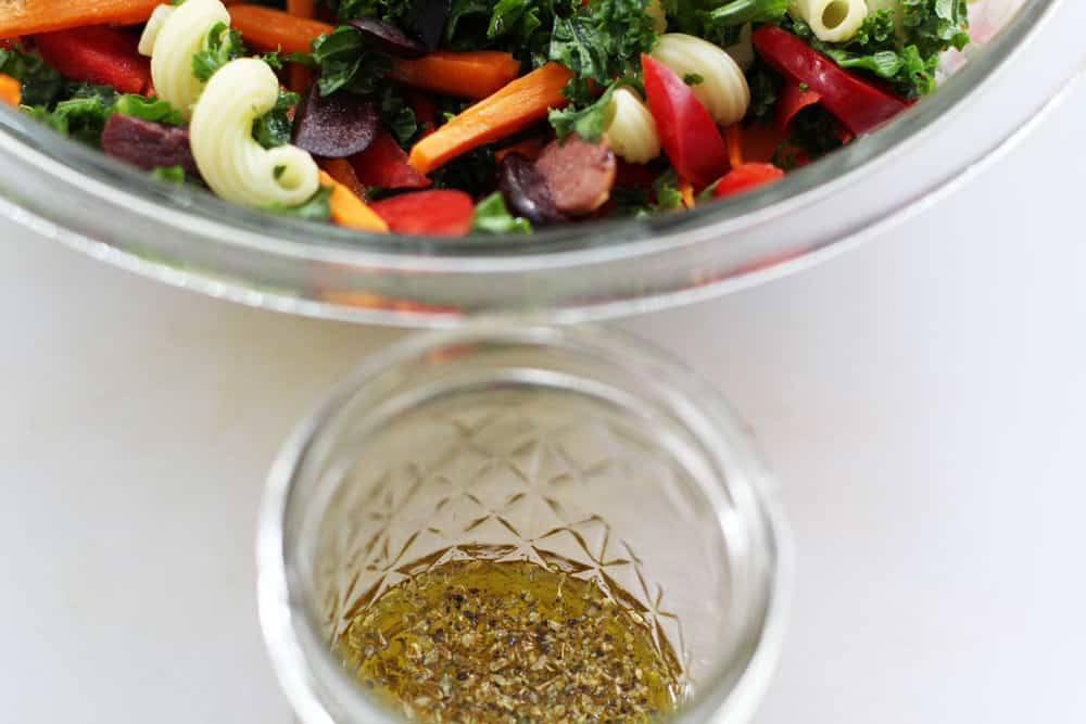 Mixing the dressing into colorful and delicious kale pasta salad | Mother Would Know