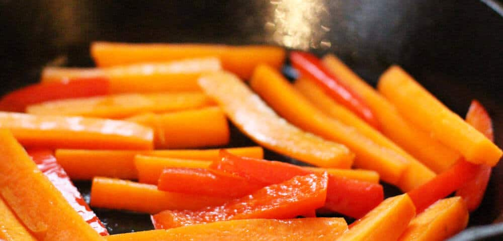 Cooking carrot and pepper matchsticks for balsamic-glazed carrots.