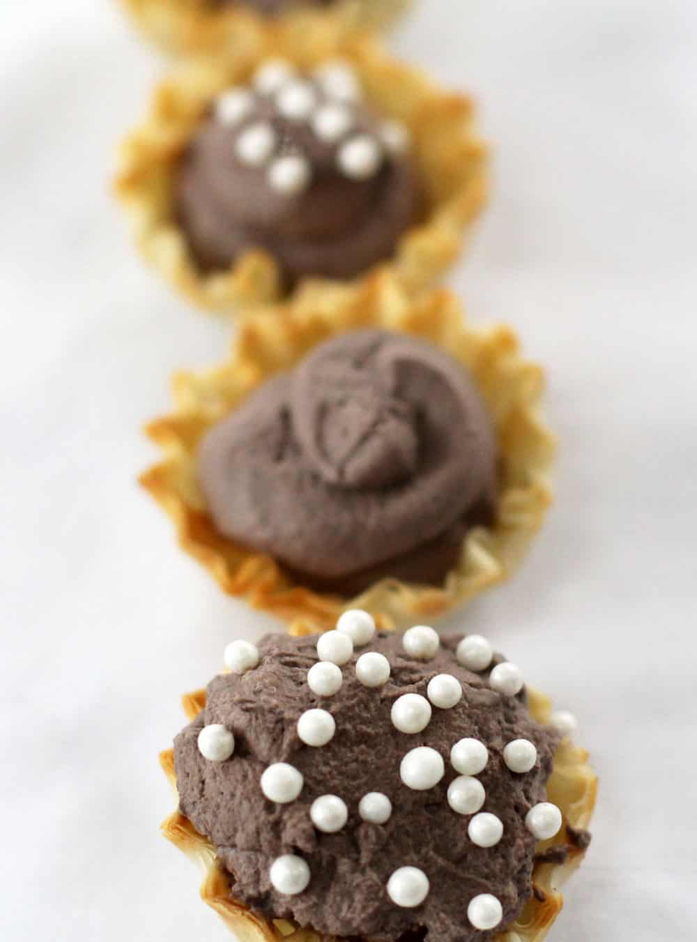 Bite sized chocolate whipped cream filled shells - a simple, yet elegant dessert.