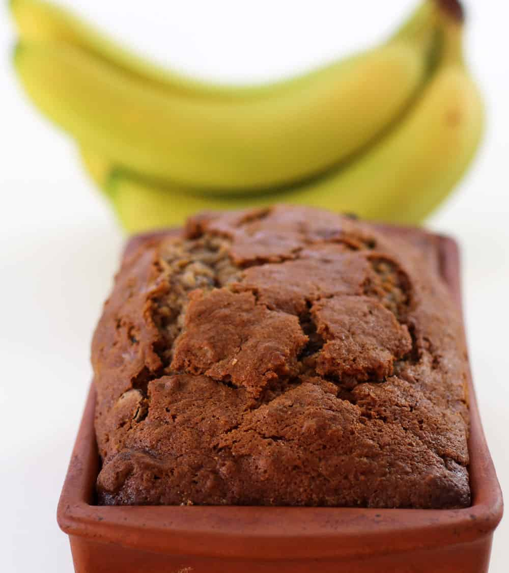 banan bread in loaf pan with bananas in background