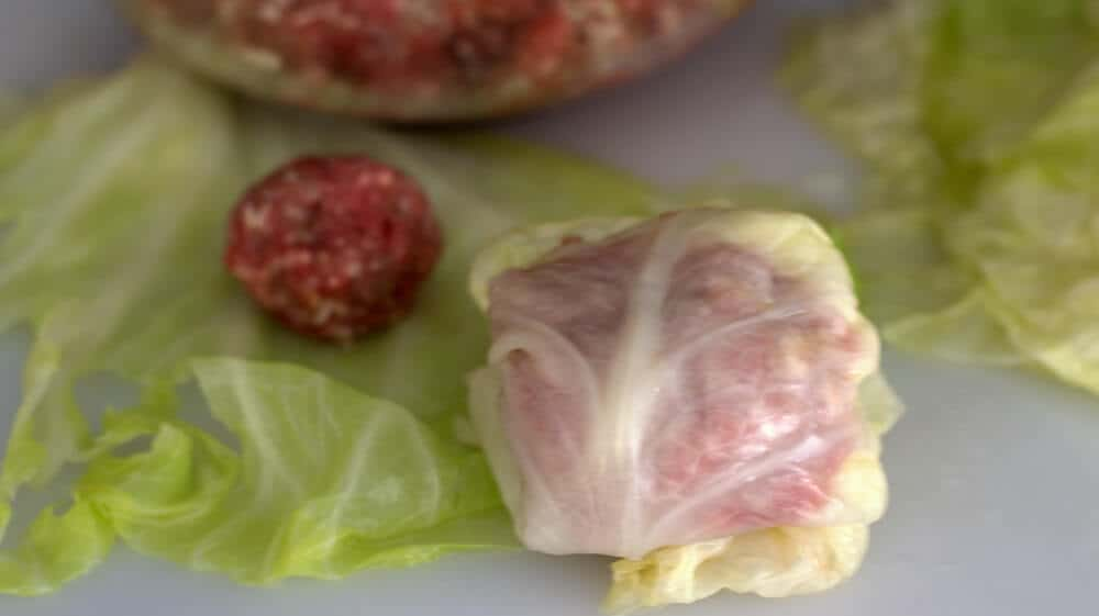 Rolling meatballs in cooked cabbage leaves for Jewish stuffed cabbage.