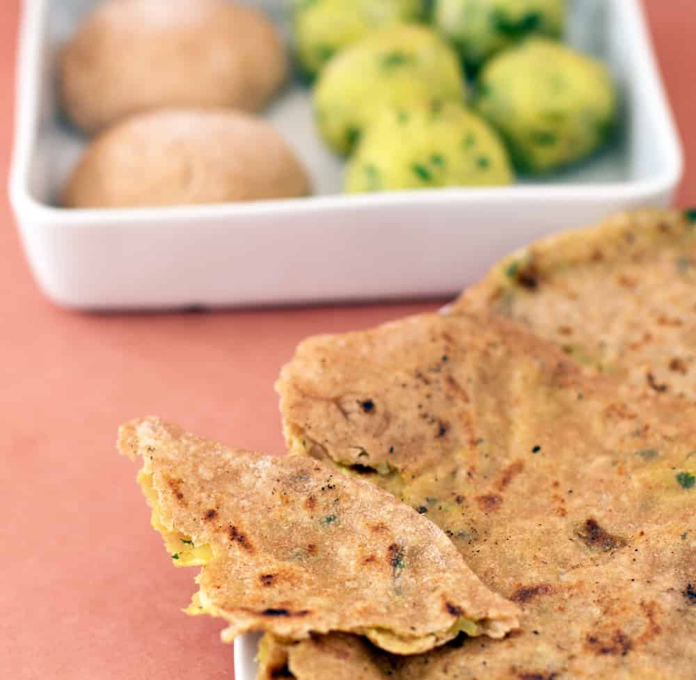 Aloo paratha, potato-filled flatbread, with the dough and filling behind.