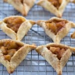Apple pie hamantaschen cooling on a wire rack
