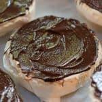 Spreading chocolate on bottom of pavlovas.