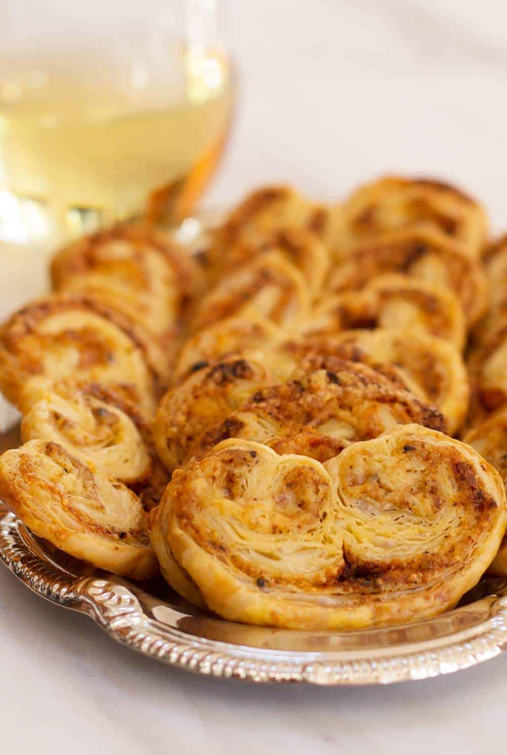 Spicy Cheddar Herb Palmiers on a tray with wine, ready for a party. | Mother Would Know