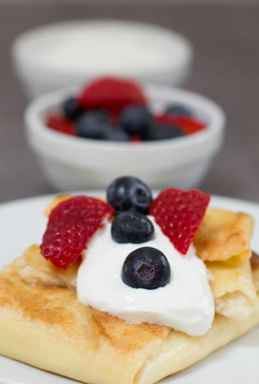 Jewish cheese blintzes for Shavuot, with sour cream and fruit