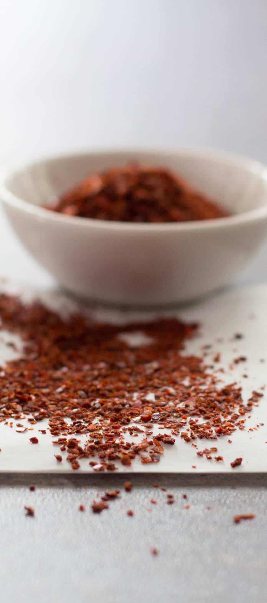 Aleppo pepper scattered and piled into a small bowl