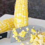 cutting corn kernels off a fresh cob