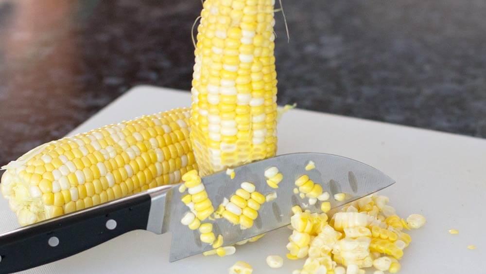cutting corn kernels off a fresh cob