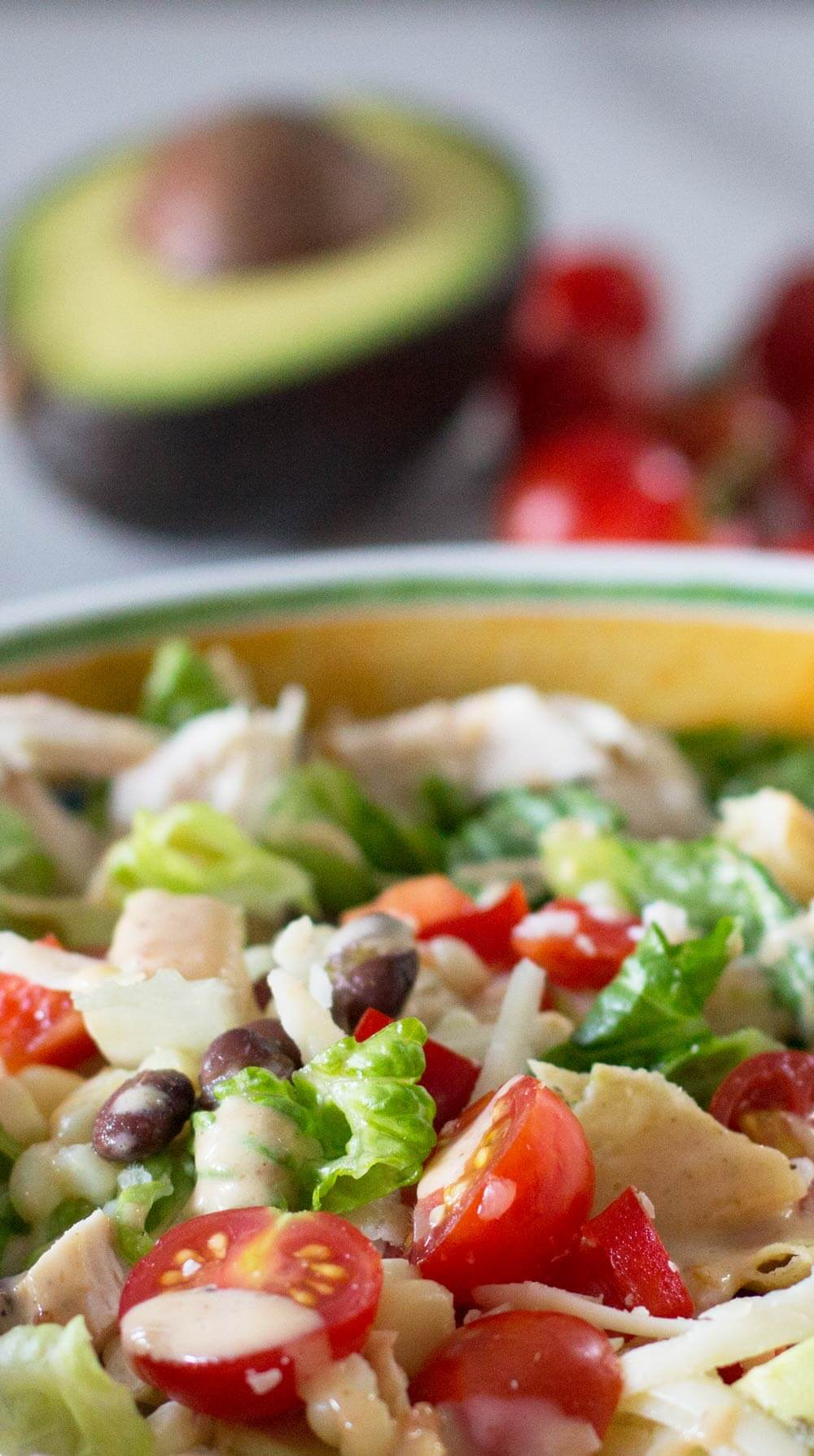 Make-Ahead Layered Southwestern Salad with tomatoes and avocado behind.