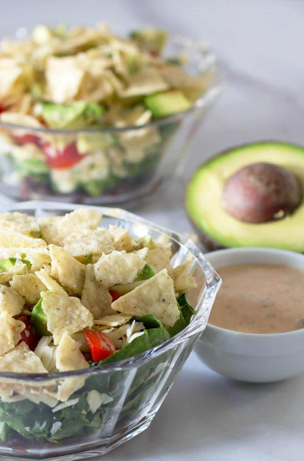 Layered Southwestern Salad with avocado and dressing on the side