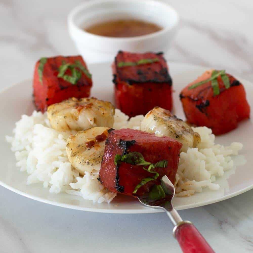 Spicy sweet sauce with Grilled Watermelon Scallop Shish Kebobs on rice.