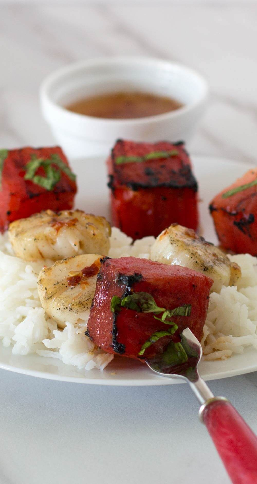 Grilled Watermelon Scallop Shish Kebobs with a watermelon cube on a fork