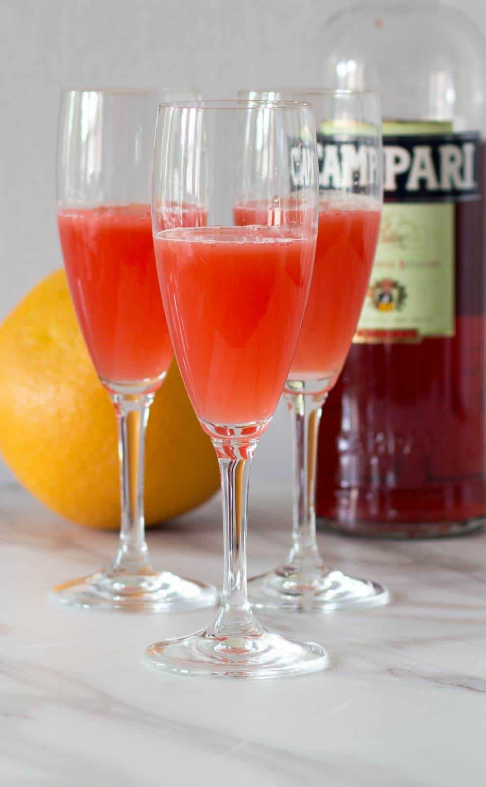 Campari grapefruit punch with oleo saccharum in front of grapefruit and Campari