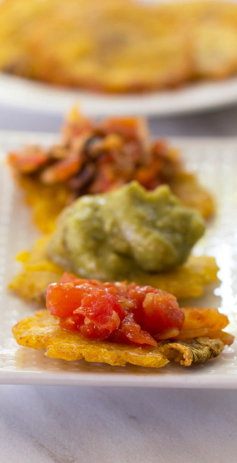 Patagones or green plantains on a plate with hogao and other toppings on top.