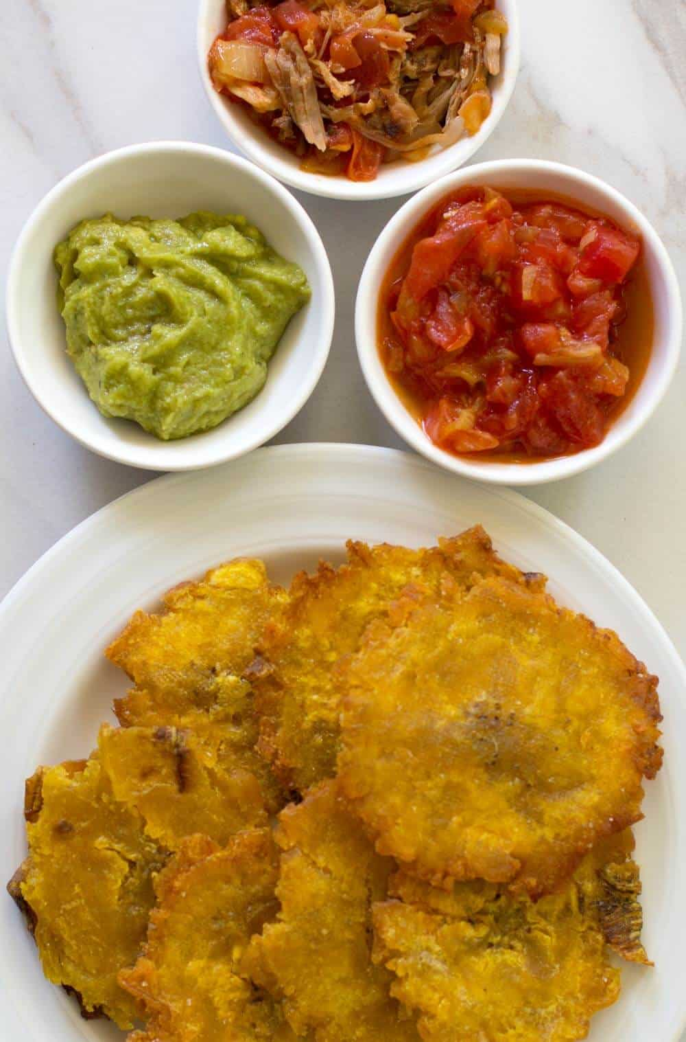 patagones or green plantains done on plate, with bowls of toppings.