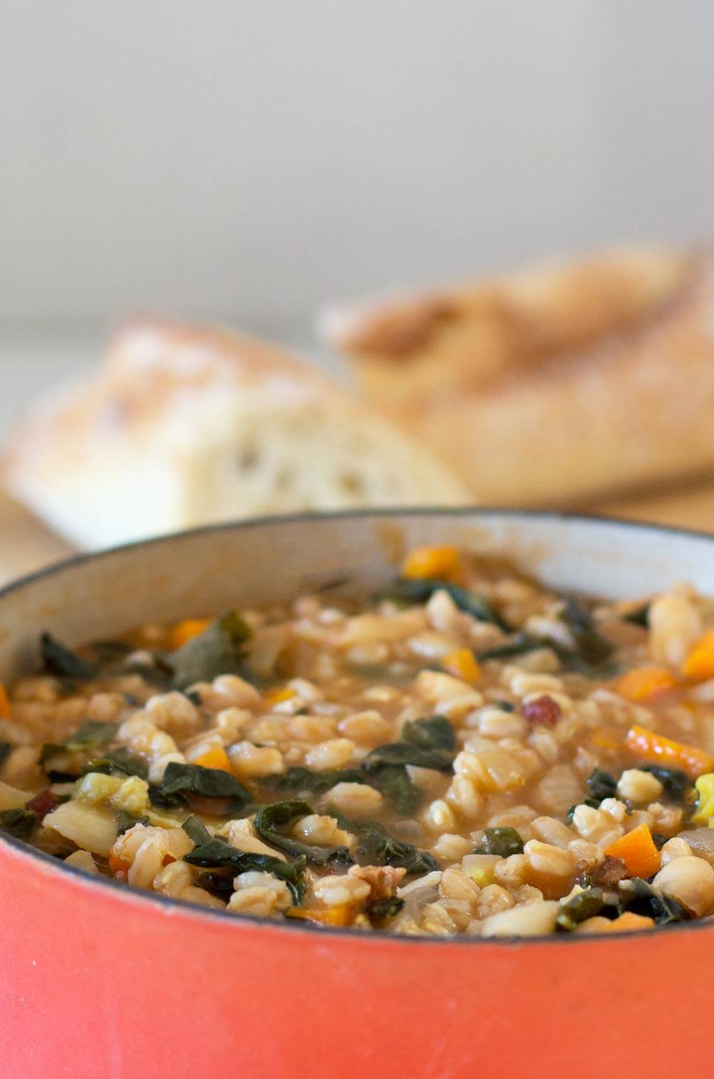 A pot of Tuscan Farro and Bean Soup with bread