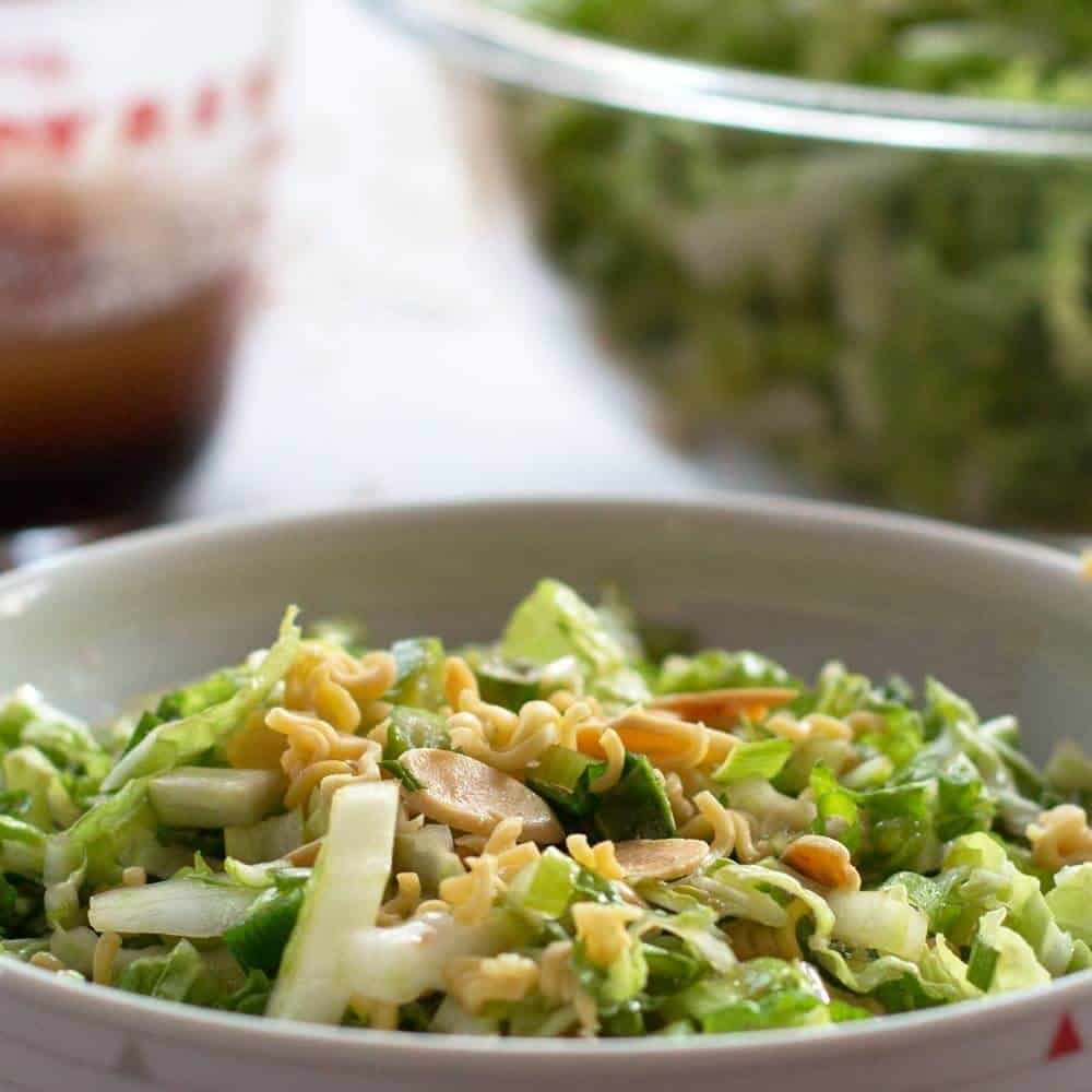 bowl of Napa cabbage salad with dressing and cabbage bowls behind
