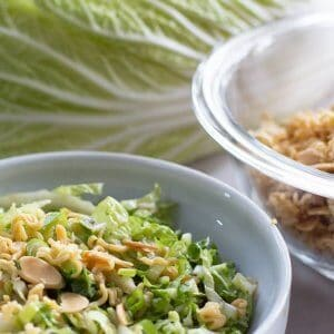 Crunchy Napa cabbage salad with a cabbage leaf and crunchies in a bowl