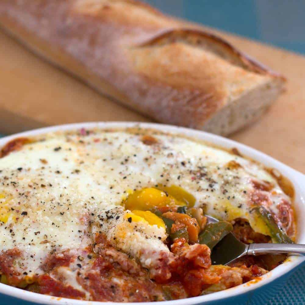 Tuscan baked eggs, with a fork opening the casserole