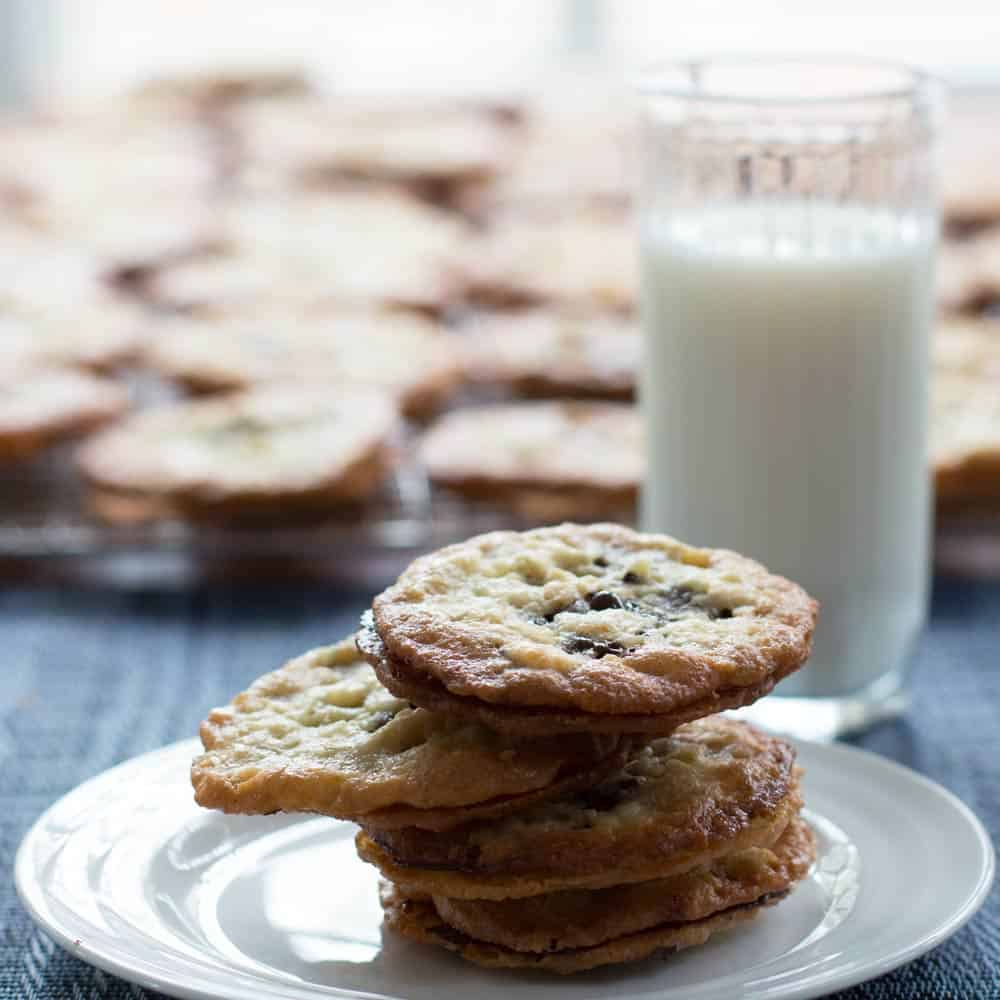 A stack of Passover chocolate florentine cookies with a glass of milk
