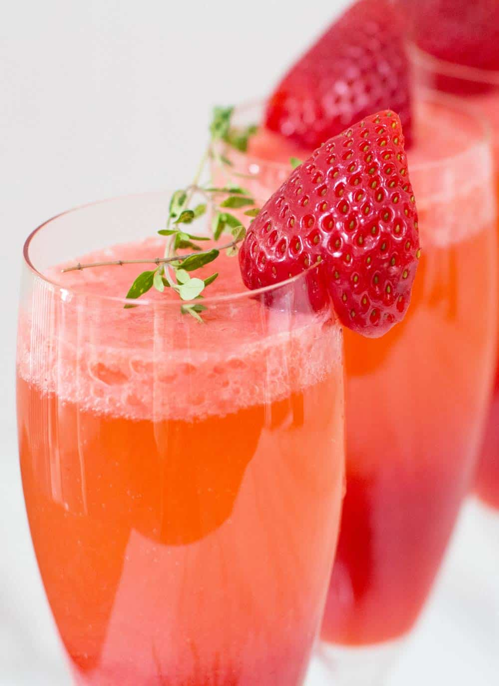 closeup of strawberry bellini with fresh thyme sprig