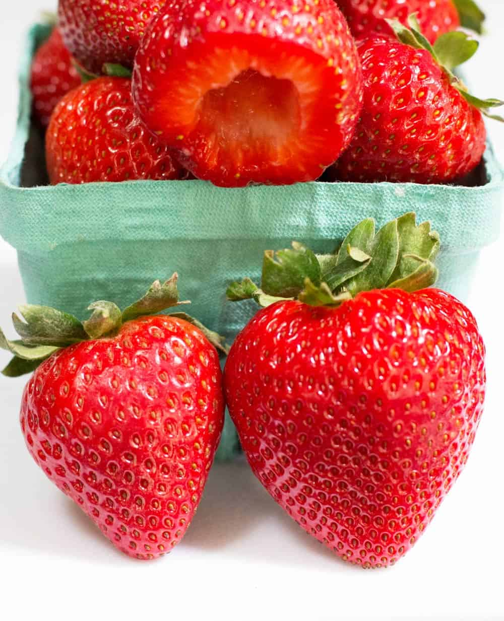 a basket of strawberries with 2 in front