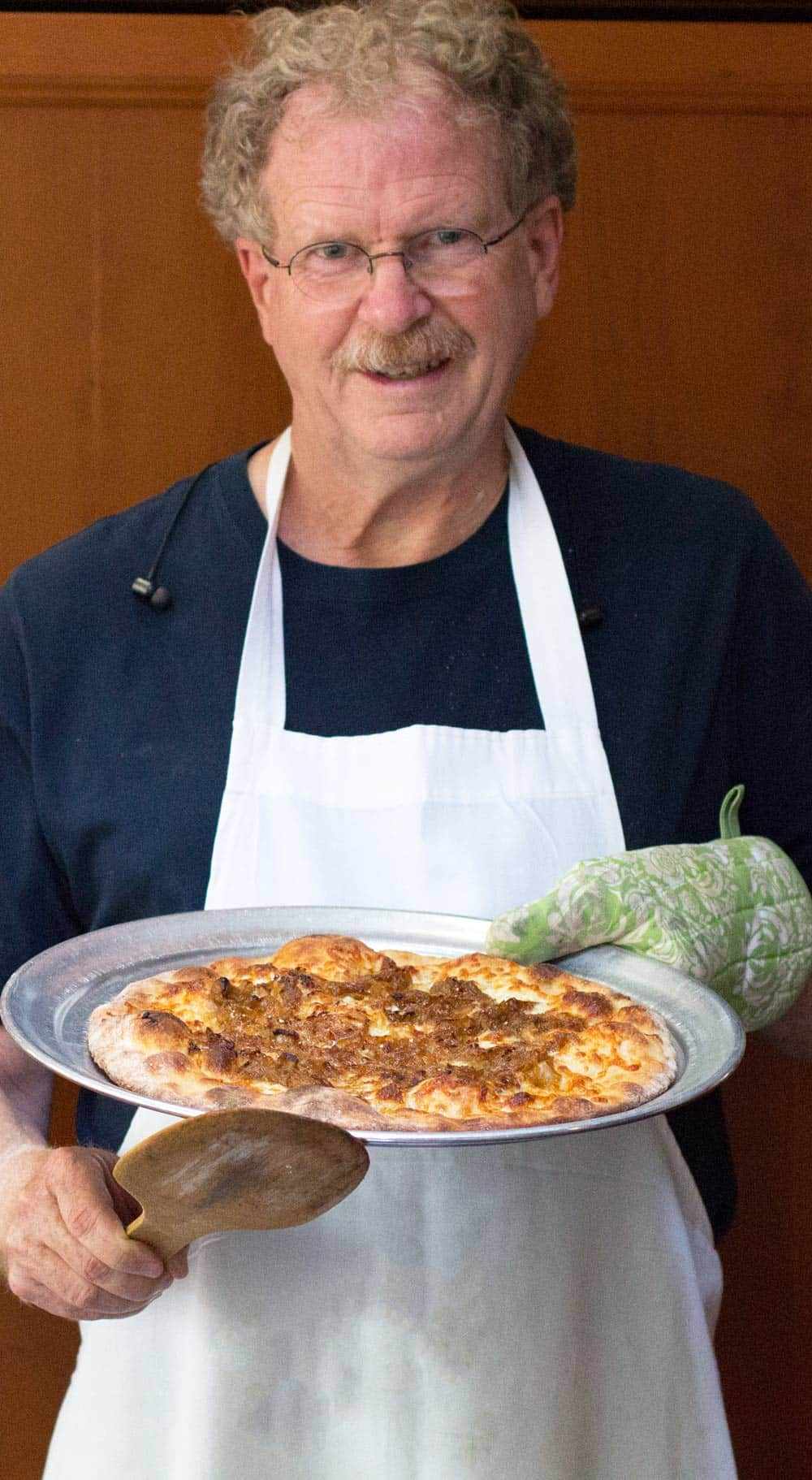 man holding a caramelized onion white pizza