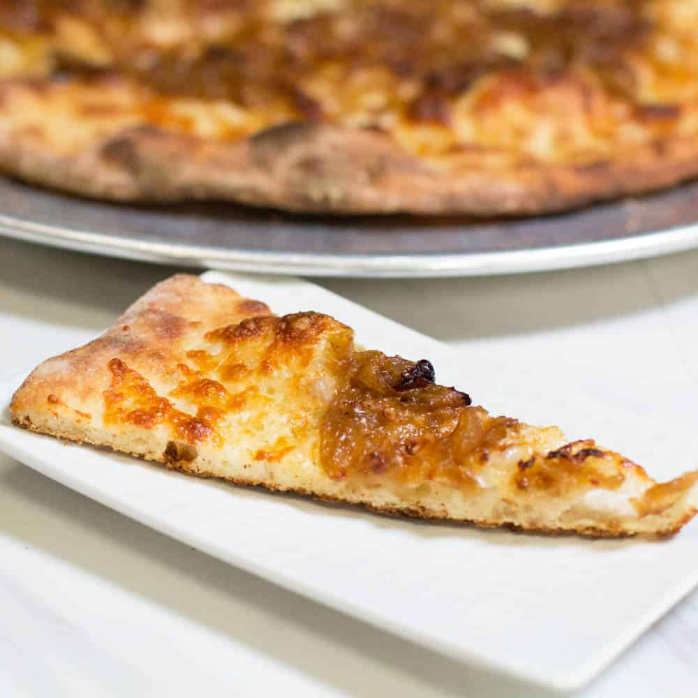 Slice of caramelized onion white pizza in front of the pie