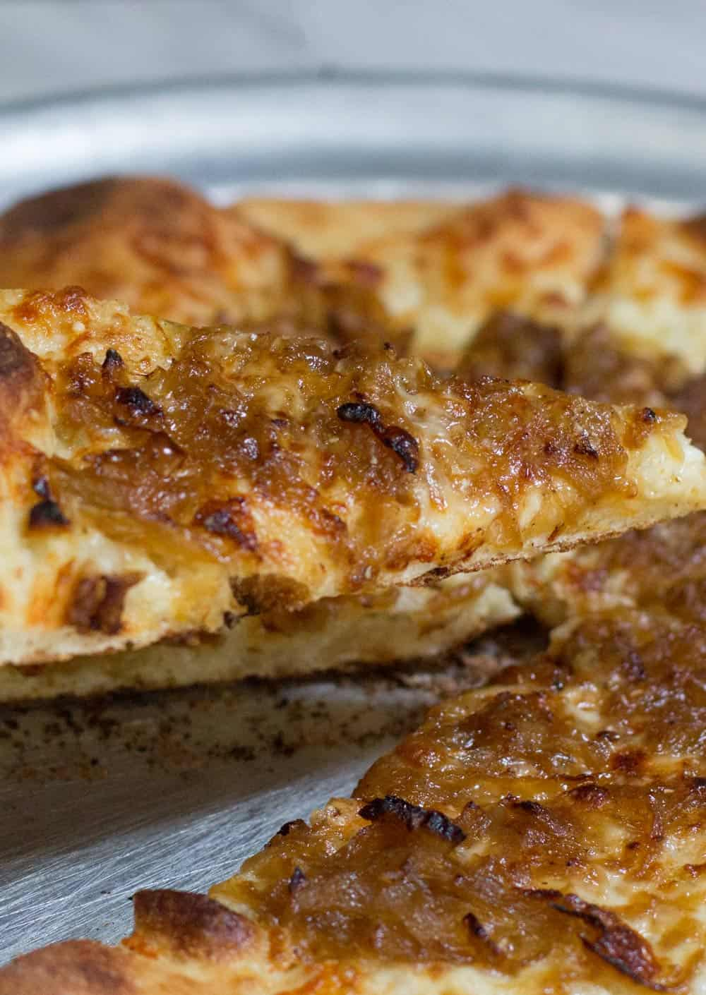 a slice of caramelized onion white pizza in front of the pie