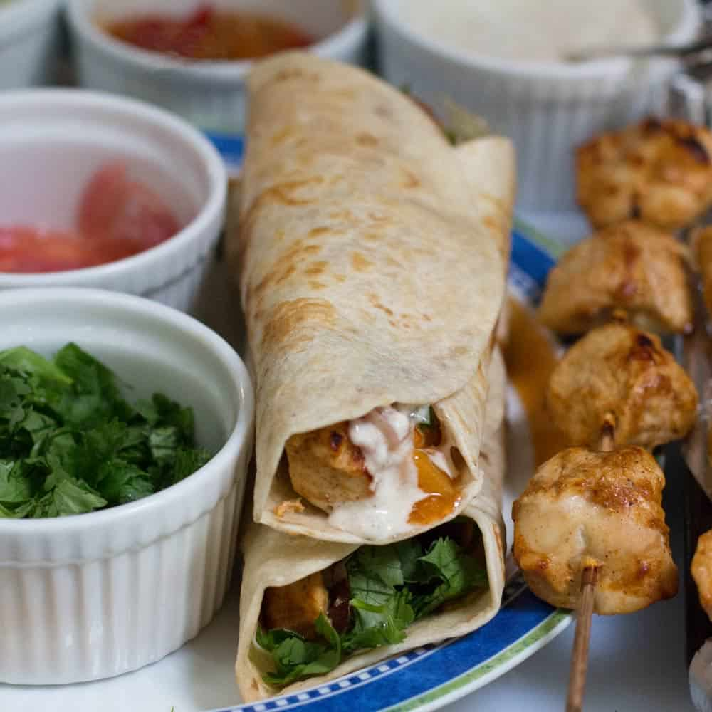 chicken kathi rolls done surrounded by chicken and toppings