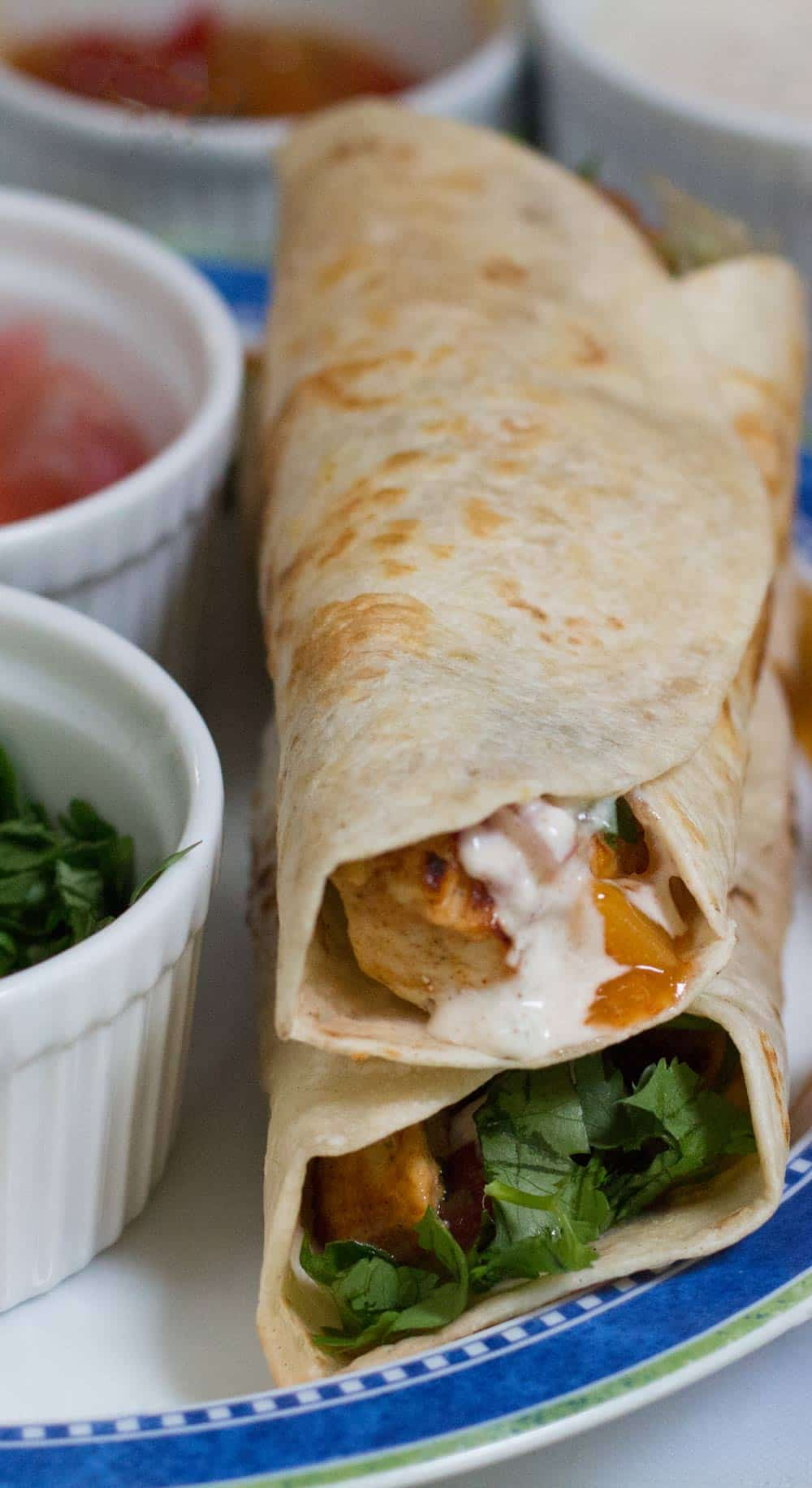 Two chicken kathi rolls surrounded by toppings