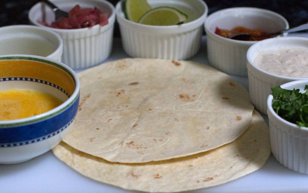 Flatbread (parathas or burrito shells) and toppings ready to make kathi rolls